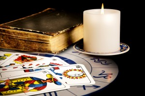 tarot cards with old book and burning candle